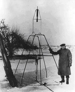 Robert H. Goddard standing next to his liquid fuelled rocket prior to its launch
